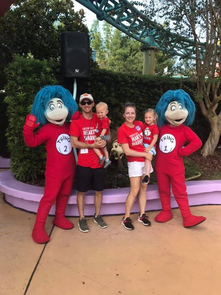 Family at Disney World posing with Thing 1 & Thing 2